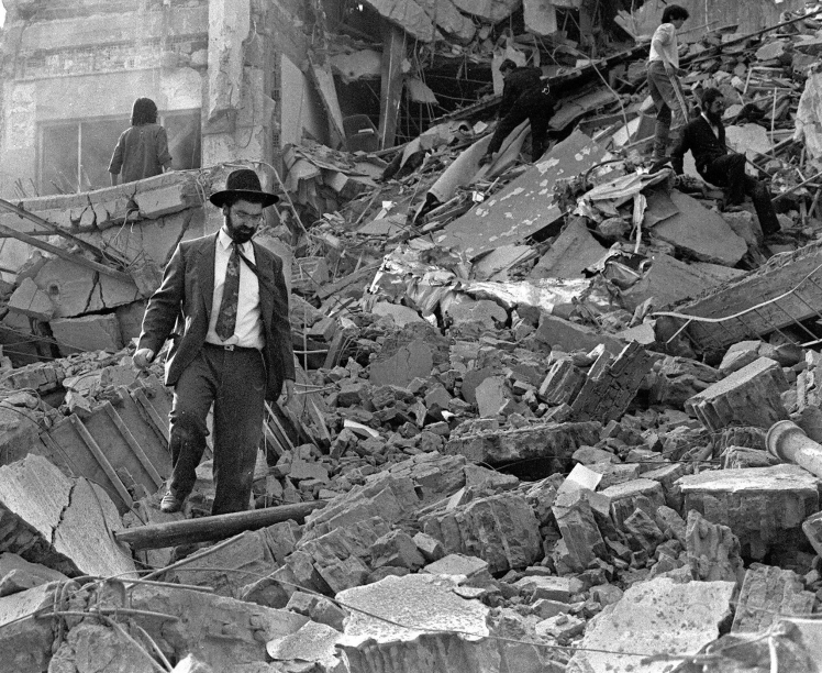 (FILE) A man walks over the rubble left